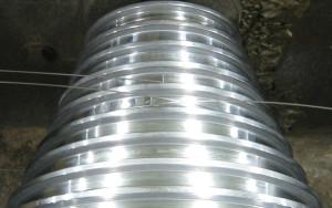 金属加工方法のひとつ。2つのロールを回転させながら貴金属を挟みつぶし伸ばすことにより板状または糸状にして鍛えていく加工。